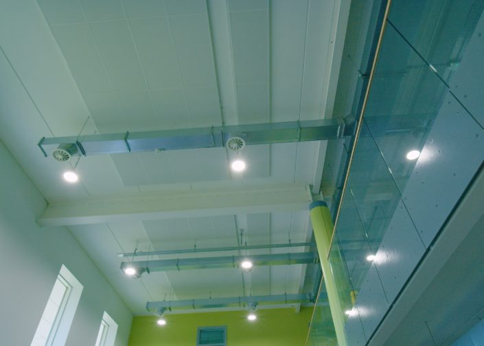 A well lit atrium using LED high bays in a large, modern Manchester high school.